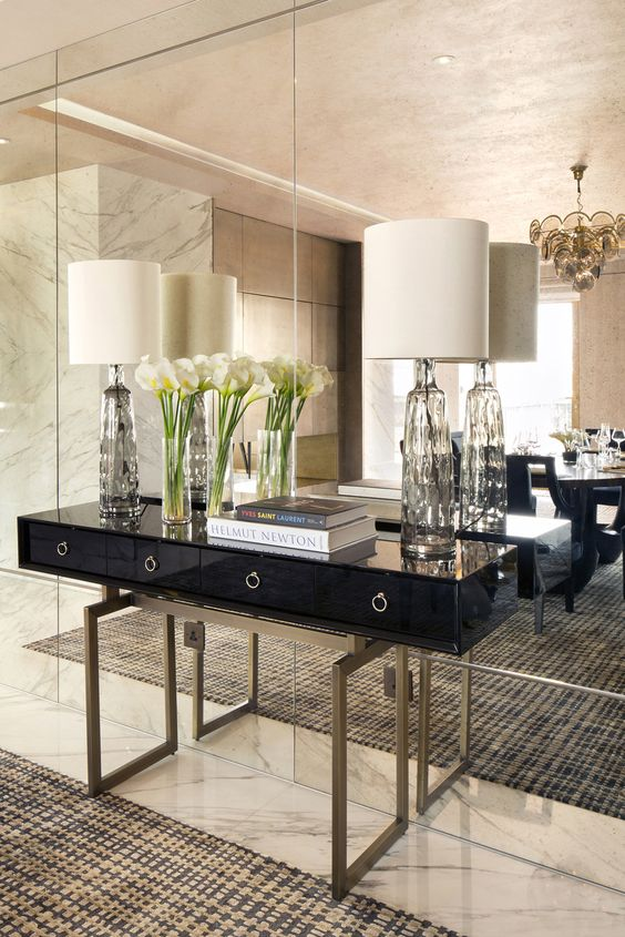 a mirror wall adds luxury to this living room together with marble and brass details