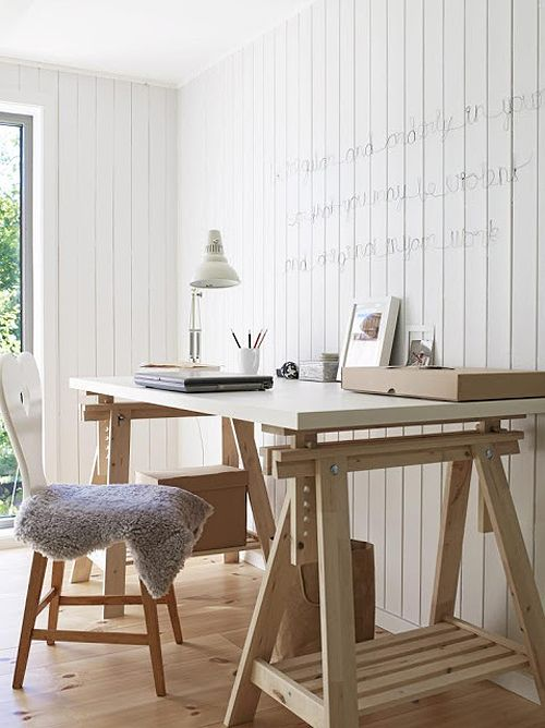 a white and light colored wood trestle desk has additional open storage compartments