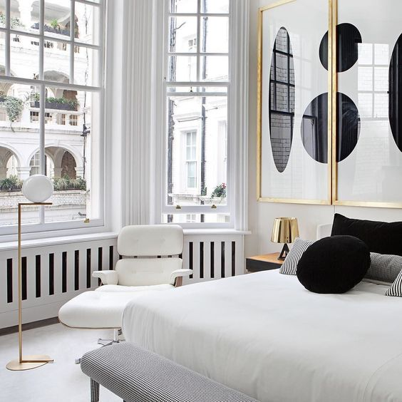 abstract black and white wall art piece in gilded frames add to the white bedroom