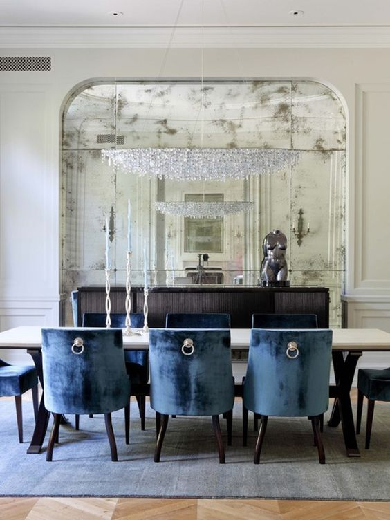 a modern dining room is made luxurious with a large crystal chandelier and an oversized faded mirror