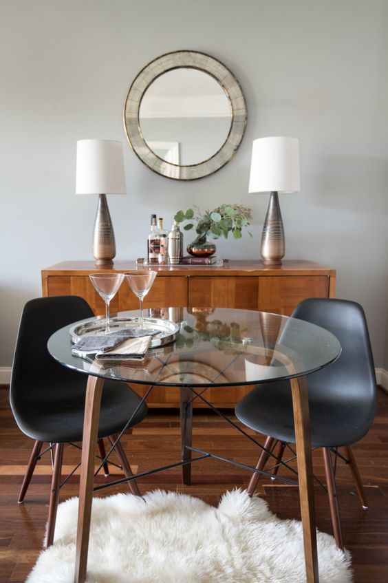 a small round table with wooden and metal legs and a glass tabletop for a cozy dining space or breakfast nook
