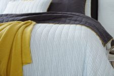 21 blue thin striped bedding with black and mustard touches for a bolder look