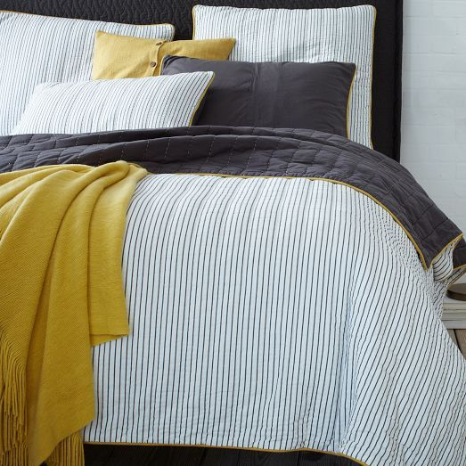 blue thin striped bedding with black and mustard touches for a bolder look