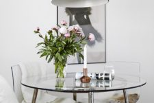 22 a chic modern round dining table with a steel framing and a glass tabletop looks cool and glam