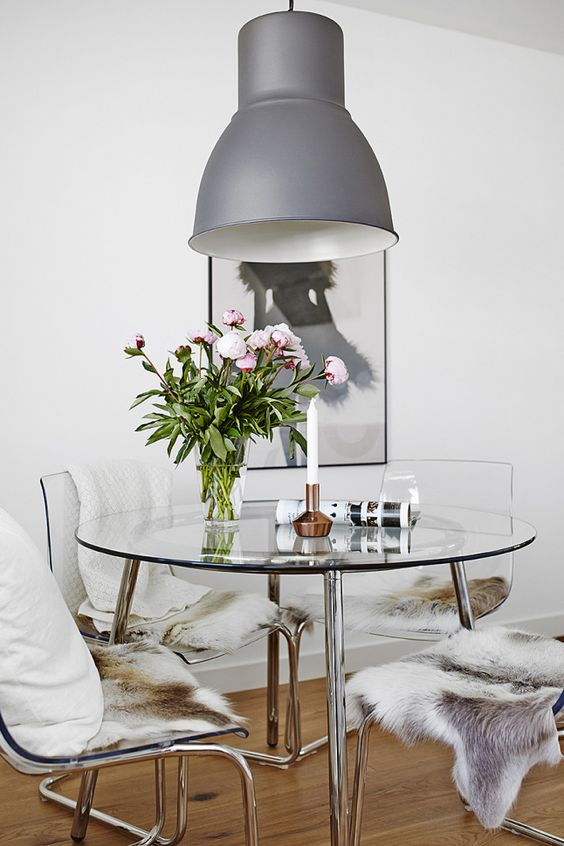 a chic modern round dining table with a steel framing and a glass tabletop looks cool and glam