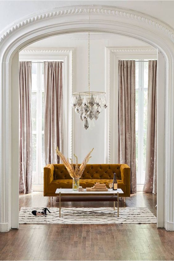 a glam living room with a chandelier, a mustard velvet sofa and blush velvet curtains create a gorgeous ambience