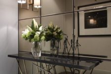 22 a smoked mirror wall, a geo base console make this entryway super modern and eye-catchy