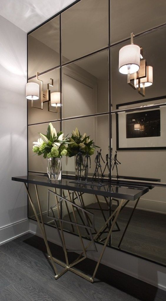 a smoked mirror wall, a geo base console make this entryway super modern and eye catchy