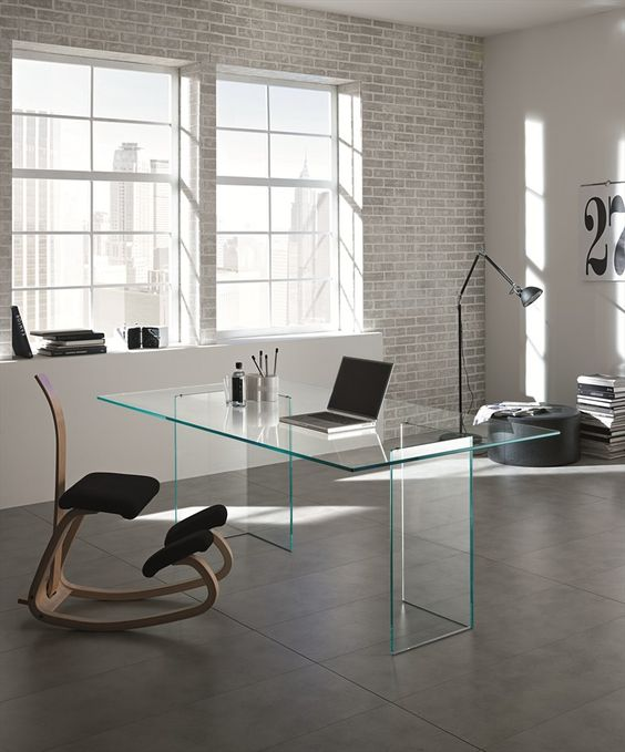 minimalist and industrial home office with a clear glass desk and an eye-catching upholstered chair