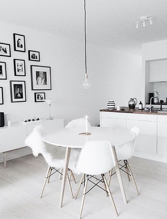 a united kitchen and dining space with a black and white gallery wall, which adds style