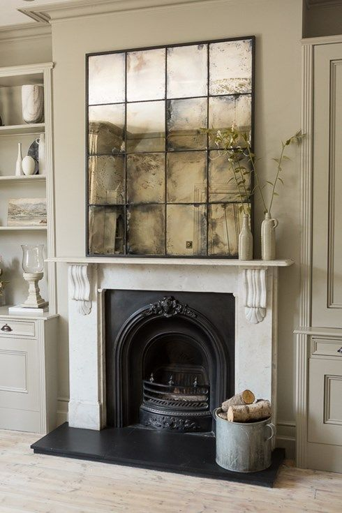 a vintage space with a fireplace is highlighted with a faded mirror over the mantel