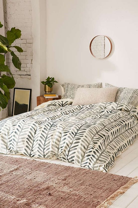 boho and mid century modern bedding with a muted green botanical print