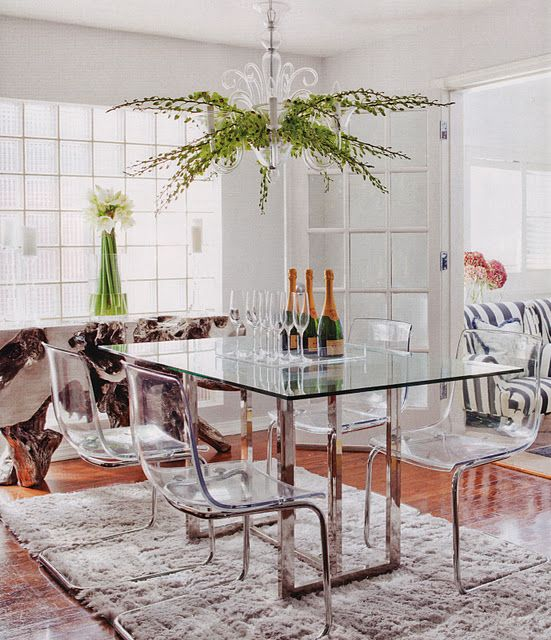 a dining table with metal legs and acrylic chairs on the same legs look modern, chic and ethereal