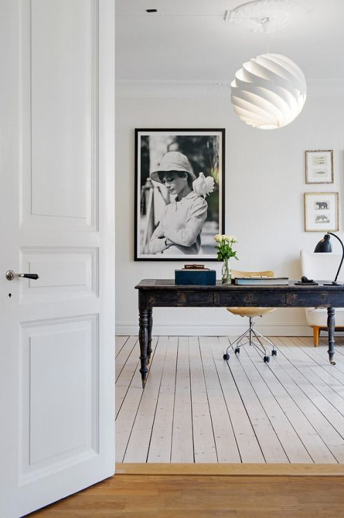 a large black antique desk stands out in an all-white space