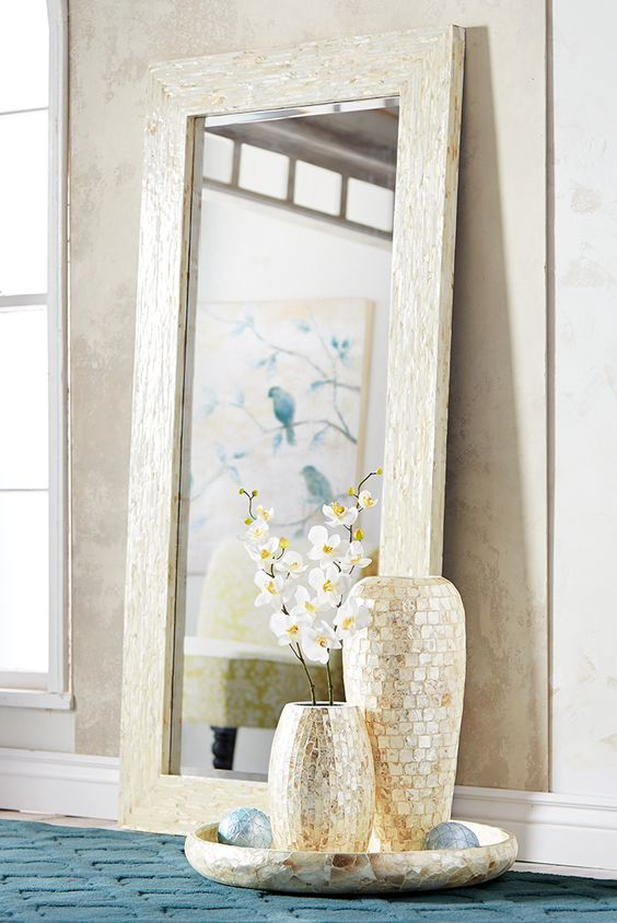 a large mother of pearl mirror and a couple of vases clad with the same material look very feminine and eye-catching