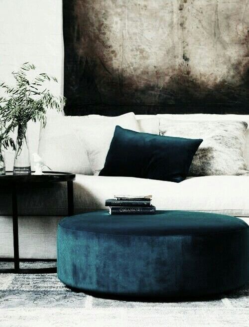 a navy ottoman and a pillow won't break the bank but will make your space fashionable and luxurious