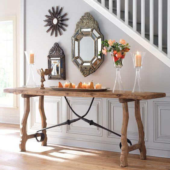 A Rustic Trestle Console Table With Blackened Metal Decor Echoes With  Vintage Metal Framed Mirrors