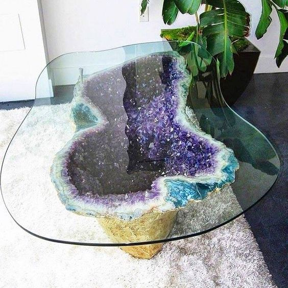 a unique coffee table with an amethyst base gilded on the outside and a matching in shape glass tabletop will be a showstopper