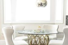 25 a glam dining space with metallic sphere pendant lamps, a brass table base and a round tabletop, comfy cream chairs
