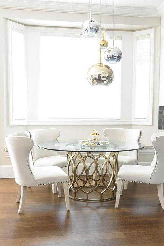 a glam dining space with metallic sphere pendant lamps, a brass table base and a round tabletop, comfy cream chairs