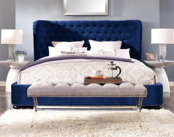 a navy velvet upholstered sofa makes a bold statement in a neutral bedroom