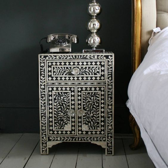 a refined black nightstand clad with mother of pearl looks vintage and very refined