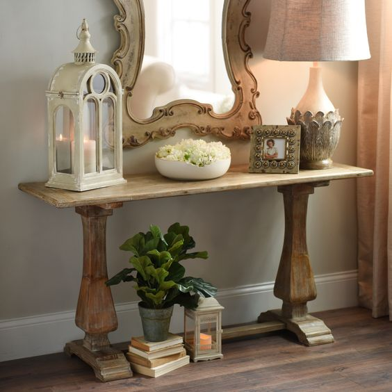 a small trestle table used as a console for a vintage-inspired entryway