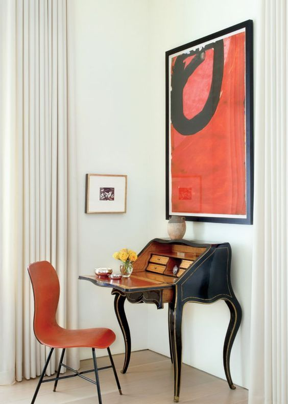 a vintage secretaire in a mid-century modern space with a bold artwork