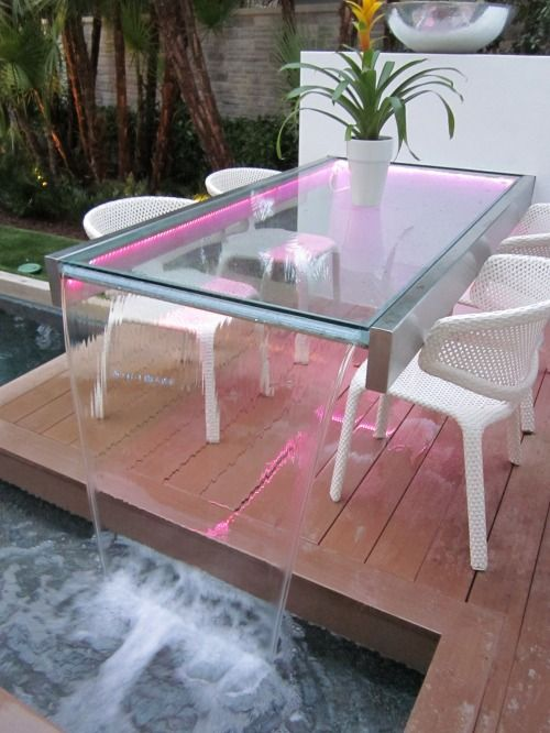 an outdoor glass table with a fountain with neon lights is a spectacular piece