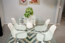 27 a glass top dining table with curved metal legs, modern white chairs and a creative pendant lamp