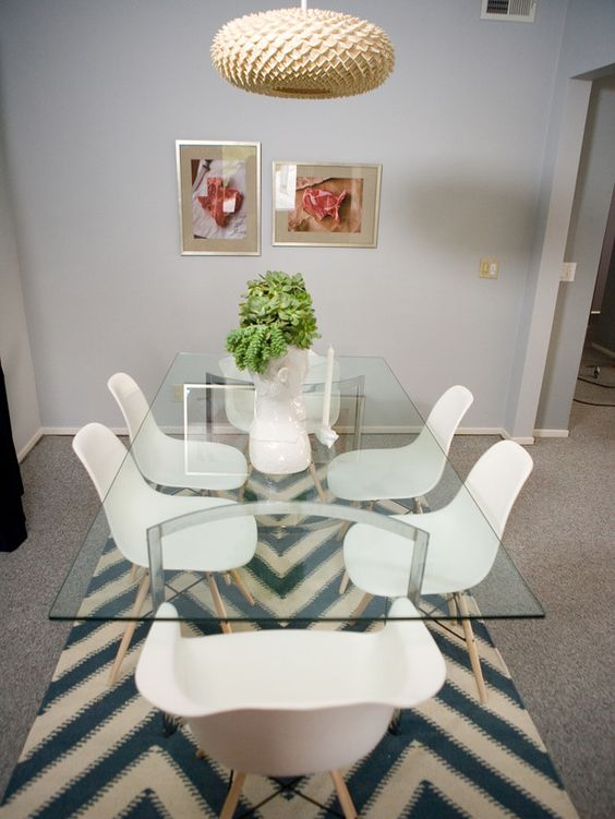 a glass top dining table with curved metal legs, modern white chairs and a creative pendant lamp