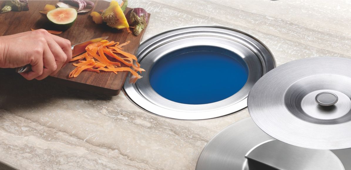 a trash can inside the kitchen island with a stylish hole for putting trash there