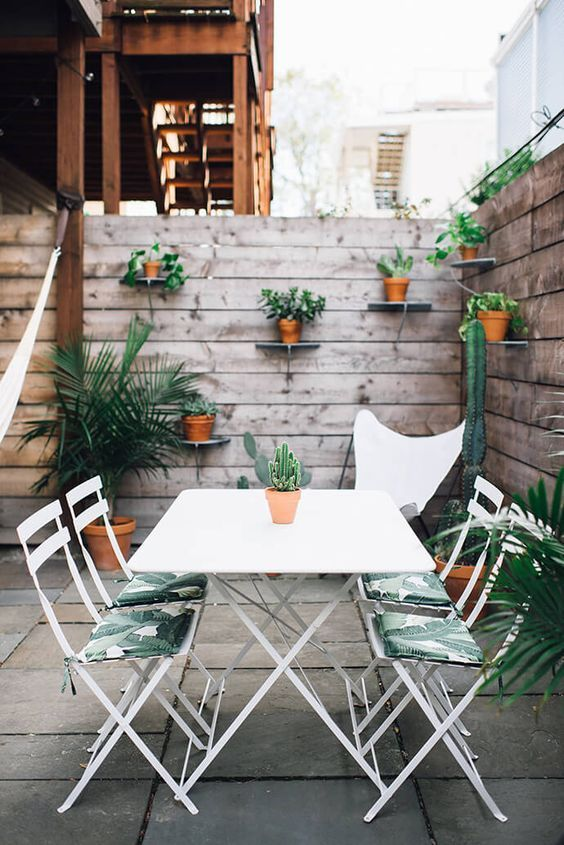 palm leaf print chairs echo with cacti and greenery and cheer up this outdoor space