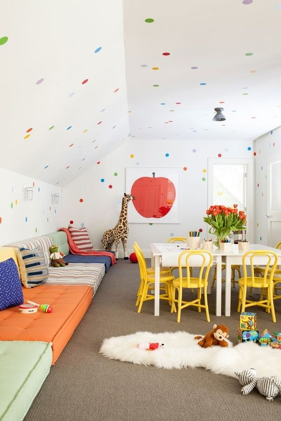 a super bold space with floor cushions along the wall and colorful polka dots looks awesome