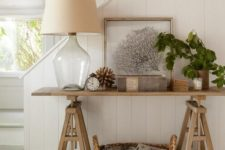 28 a wooden trestle table used in an entryway or living room as a console, a basket for additional storage