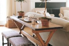 29 rustic wooden trestle table is repurposed into a console that adds warmth to this living room