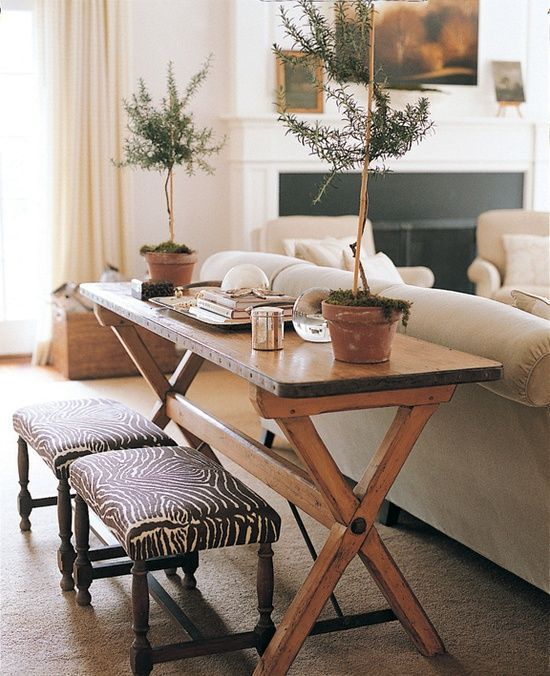 rustic wooden trestle table is repurposed into a console that adds warmth to this living room