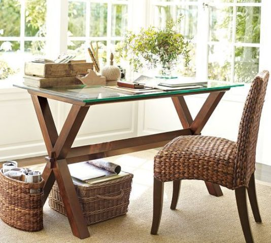 a rustic desk with dark stained wood trestle legs and a glass tabletop