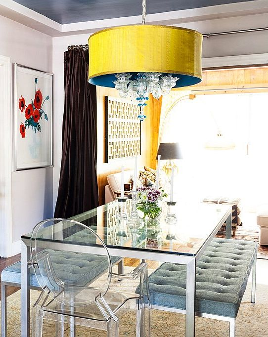 an eye-catchy dining space with a dining table on a metal framing and legs and a glass tabletop and upholstered benches