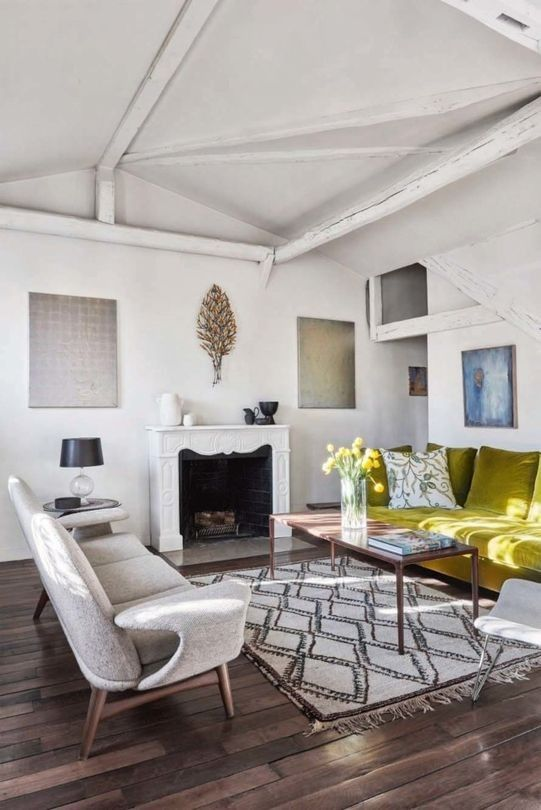 Most of the apartment is painted white, and there are wooden beams on the ceiling, the living room features an antique fireplace, comfy furniture and a statement - a mustard sofa