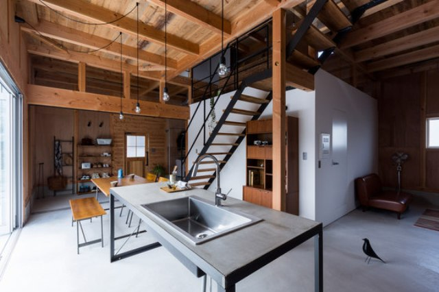 The kitchen and dining spaces are united with the entryway, there's a metal functional space, a wood and black metal dining set and some open shelving