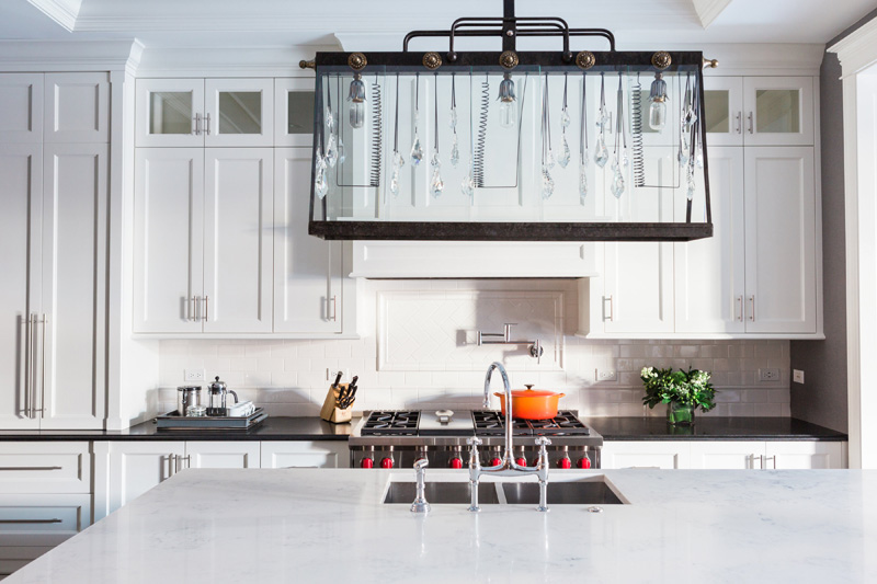 The kitchen is white and rather traditional but the accent is made with a unique lighting fixture that blends crystal hangings and industrial details