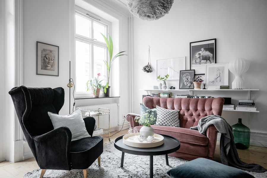 The living room features a pink sofa, a black chait, a fluffy pendant lamp and some shelves, looks very welcoming