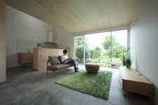 02 The living room is centered around the glazed wall, and the kitchen is placed in the corner, it's separated with a wood clad kitchen island