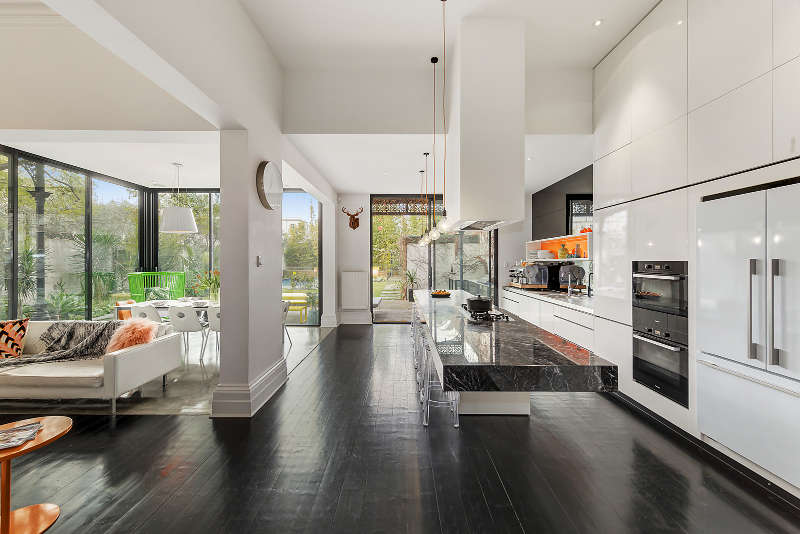 The modern open layout includes a kitchen, a dining space and a living room, there are glazed walls and some orange touches