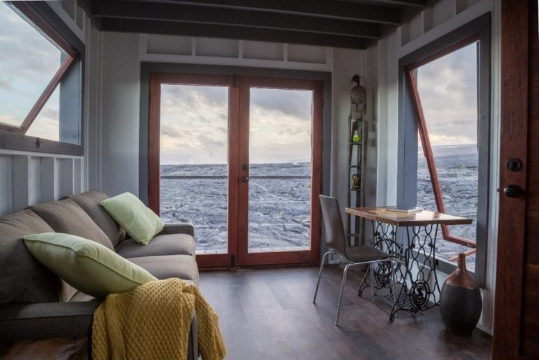 There are many windows and glass doors to enjoy the unique views and lava, there's a working space with a vintage desk at the window and a large sofa to have a look outdoors