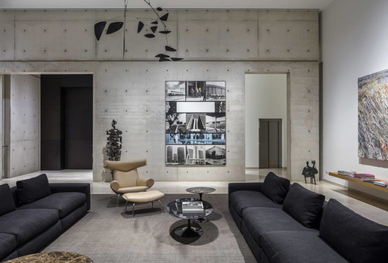 This is the living room that features black sofas, concrete walls and bold artworks including a human figure on the wall