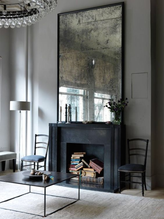 a black fireplace is repurposed into a book storage space