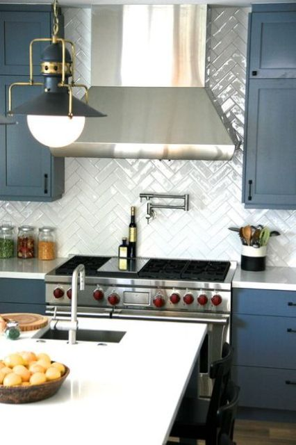 a glossy white tile herringbone backsplash makes the matte blue cabinets stand out