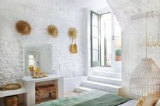 02 a mediterranean bedroom features whitewashed brick and tiles on the floor, everything is white except for bedding